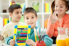 young brothers and sisters together  learn math on abacus - stock photo