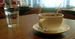 Glas of water cup of coffee in a white cup on wooden table Stock Footage