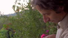 Younger to Middle aged man watering an outdoor plant with a green watering can. Stock Footage
