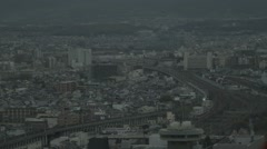Houses, buildings and train moving on bridge in the city of Kyoto Stock Footage
