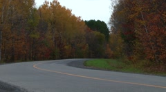 Motorcycle corners away from camera on rural country road Stock Footage
