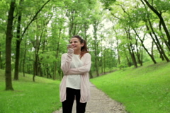Woman standing in the park and talking on loudspeaker Stock Footage