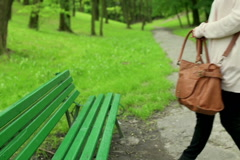 Woman coming to the park and start reading book on the bench Stock Footage