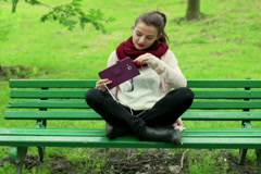 Woman sitting on the bench in park and start listening music Stock Footage
