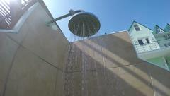 Outdoor poolside shower falling water at hotel swimming pool POV Stock Footage