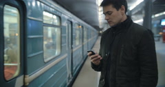 Man typing sms standing on the subway platform - stock footage