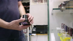 Customer looking for new compact camera at photographic equipment store Stock Footage
