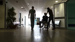 Pushing a man in a wheel chair, backlighting. Stock Footage