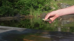 Man puts small fish back into water Stock Footage