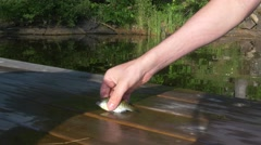 Man shows off small fish on dock Stock Footage