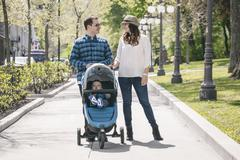 Young family with baby strollers on city walk Stock Photos