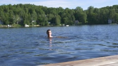 Man treads water out of focus right off of cottage dock Stock Footage