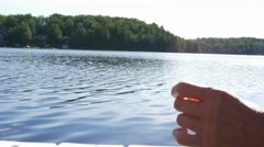Hands on cottage dock in front of lake Stock Footage