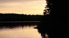 Smooth sunset pan of forest shoreline and island at sunset Stock Footage