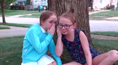 Two girls tell secrets to one another in their front yard by a tree as two young Stock Footage