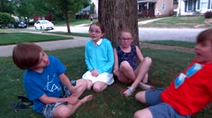 Four kids sit on the green grass by a tree in their front yard and play Stock Footage