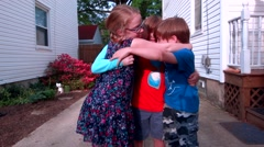 Four kids hug one another in their drive way Stock Footage