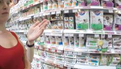 Shop assistant helps customer to choose premium cat dry food at pet store Stock Footage