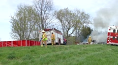 4K UHD - Portable water tank with firemen at scene of fire Stock Footage