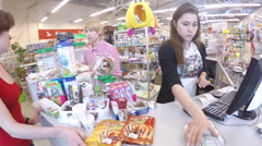 Buyer pays for the goods at  pet store checkout counter buying food for cat Stock Footage