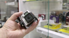 Customer looking for GoPro HERO 4 camera at photographic equipment store Stock Footage