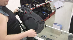 Customer looking for new camera backpack at photographic equipment store Stock Footage