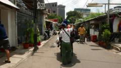 Peddler push stall cart through small street, follow camera Stock Footage