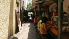 Indonesian eatery in narrow alley, camera move forward to shaded Stock Footage