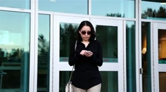 Asian woman reading mobile phone message at Douglas college parking lot Stock Footage