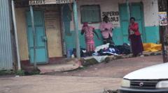 Woman knitting clothes on street Africa town, Maralal, Samburu, Kenya, pan left Stock Footage
