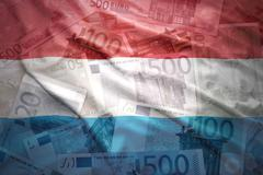 Stock Photo of colorful waving luxembourg flag on a euro money background