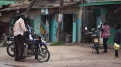 Men on motorcycles in Africa town Maralal, Samburu, Kenya, long shot Stock Footage