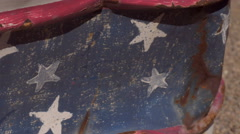 Close up of American Flag painted on a dented rusty metal trash can dolly shot Stock Footage