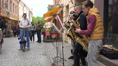 Boy trio play saxophones on street music day festival. 4K Stock Footage