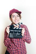 Smiling girl with movie clapper on white background - stock photo