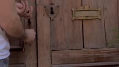 Man unlocks old wooden door with keys and enters home in slow mo Stock Footage