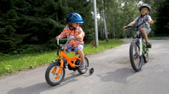 Cute little boy in helmet riding bicycle, his older brother overtaking him Stock Footage