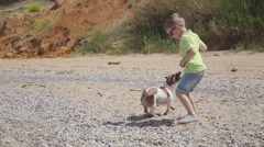 Cute little boy in sunglasses running on the beach with his pet near the sea in Stock Footage