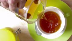 Man's hand pours sweetener in a cup of tea Stock Footage