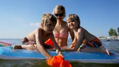Mother with two kids swim in sea, boys sitting on inflatable mattress Stock Footage