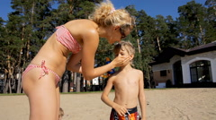Mother and son applying sun screen lotion on the beach. Healthy sunbathing. Stock Footage