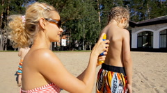 Young woman applying sun block on the back of little boy on the beach. - stock footage