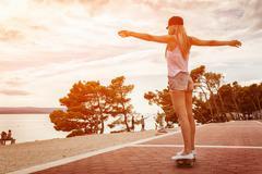 Young carefree woman riding a skateboard along the coast - stock photo