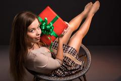 Sensual sexy attractive girl sits on a chair with gift in her hands Stock Photos