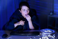 Frighten woman watching thriller - stock photo