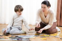 Kid solving a floor puzzle at home being helped by his mother Stock Photos