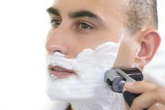 Young man shaving using electric shaver Stock Photos