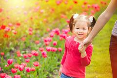 Little girl cheerfully walking in summer urban park holding hand of mother Stock Photos