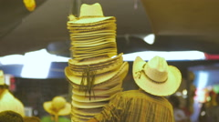 Man carrying many cowboy hats in a busy market in Mexico - stock footage