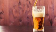 Pouring beer in glass with white foam on wood background Stock Footage